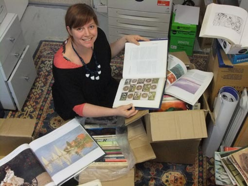 Jacqui Moyes, Arts in Corrections Advisor, browses through a donation of art books
