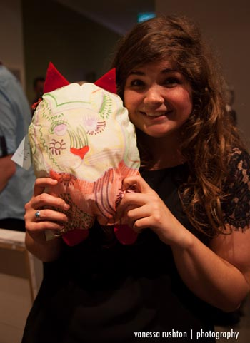 Julie Sarros with her new cat pillow made by Alpha Art Studio's Shafiq Sos