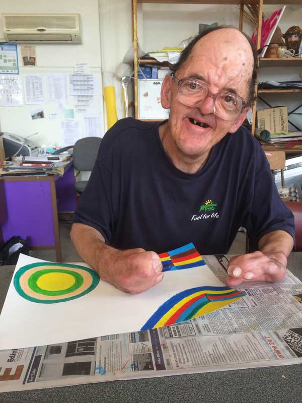 Robert, an artist at Artspace, works on one of his brightly coloured geometric designs