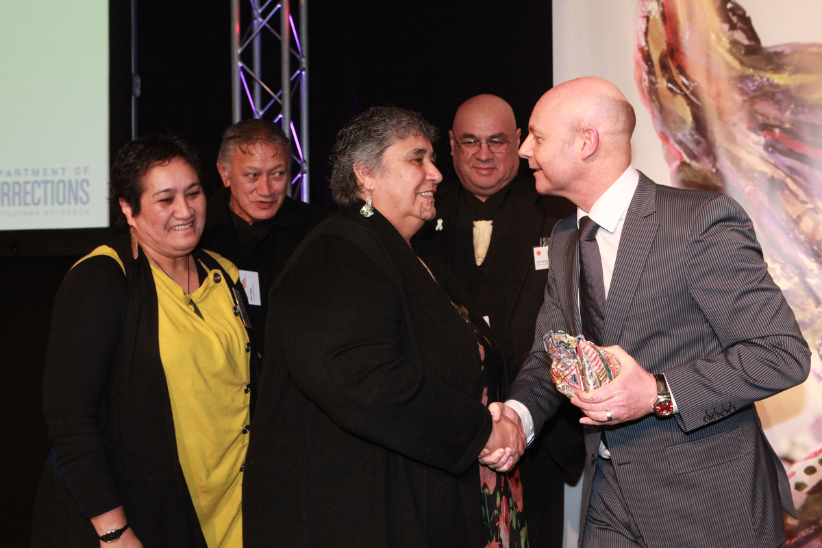 Ray Smith presents the Big 'A' Prison Arts Community Award to recipients from Waihopai Runaka