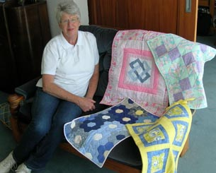 Volunteer Justine Jones with some of the quilts made for the neonatal ward at Middlemore Hospital